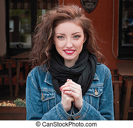 portrait of happy young woman on street cafe background