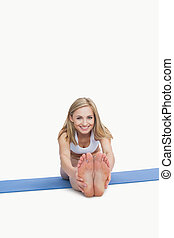 Portrait of happy young woman performing stretching exercise on yoga mat over white background