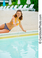 Portrait of happy young woman playing with water in swimming poo