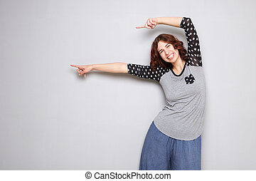 happy young woman pointing fingers at copy space on gray background