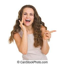 Portrait of happy young woman pointing on copy space