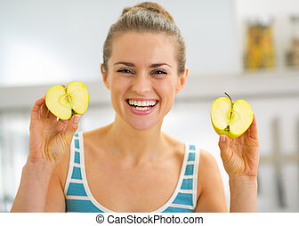 Portrait of happy young woman showing apple slices