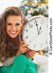 Portrait of happy young woman showing clock in front of...