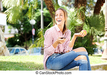 happy young woman sitting in park eating apple