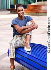 happy young woman sitting on bench outdoors