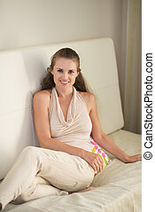 Portrait of happy young woman sitting on couch