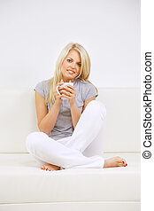 Portrait of happy young woman sitting on sofa, holding coffee cup