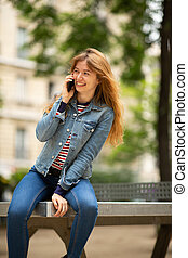 happy young woman sitting outside in park talking with cellphone