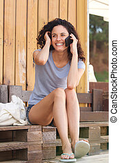 happy young woman sitting outside talking with cell phone