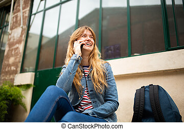 happy young woman sitting outside talking with cellphone