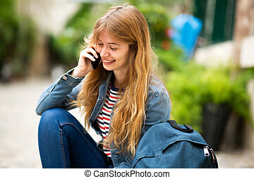 happy young woman sitting outside talking with mobile phone