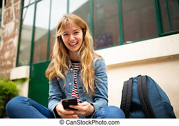 happy young woman sitting with mobile phone and bag