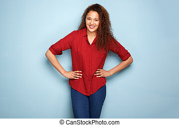 happy young woman smiling against blue background