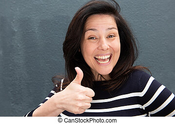 happy young woman smiling with thumbs up hand gesture