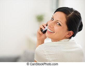 Portrait of happy young woman speaking cellphone