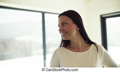 Portrait of happy young woman standing in new home. Slow motion.