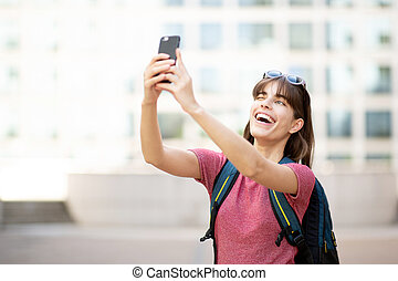 happy young woman taking selfie with mobile phone outside