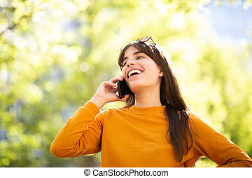 happy young woman talking with cellphone in park