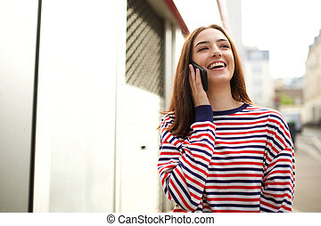 happy young woman talking with mobile phone in city