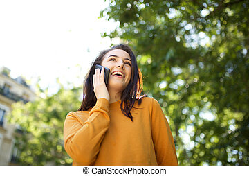 happy young woman talking with phone in the park