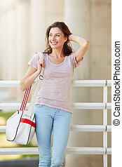 happy young woman traveler smiling with bag outdoors