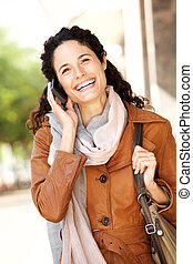 happy young woman walking with cellphone