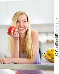 Portrait of happy young woman with apple in kitchen