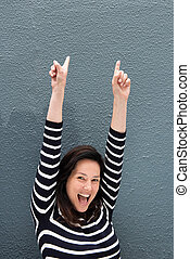 happy young woman with arms raised pointing fingers up