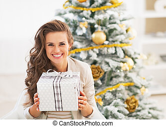 Portrait of happy young woman with christmas present box