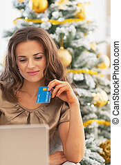 Portrait of happy young woman with credit card and laptop near christmas tree