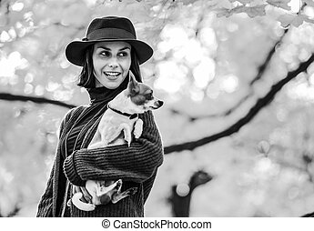 Portrait of happy young woman with dog outdoors in autumn lookin