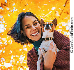Portrait of happy young woman with dog outdoors in autumn