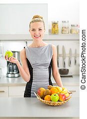 Portrait of happy young woman with fruits in modern kitchen