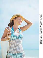 Portrait of happy young woman with hat and bag on sea shore