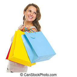 Portrait of happy young woman with shopping bags looking on copy space