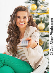 Portrait of happy young woman with tv remote control in front of christmas tree