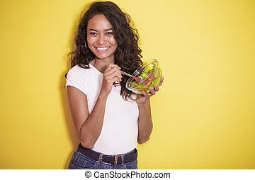 healthy asian woman eating a bowl of salad