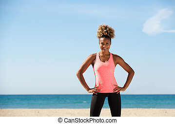 healthy black young woman standing with hands on hips at the beach