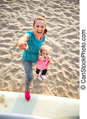 Portrait of healthy mother and baby girl on beach showing thumbs