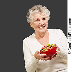 portrait of healthy senior woman holding cereals bowl over black background