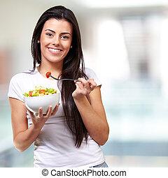 portrait of healthy woman eating salad indoor