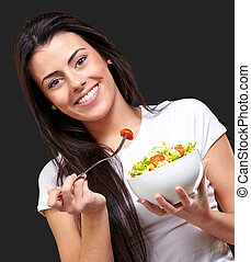 portrait of healthy woman eating salad against a black background