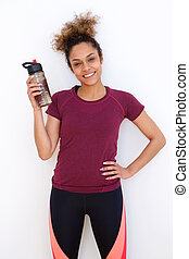 healthy young african american woman holding water bottle against white wall