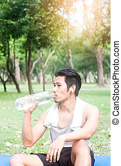 portrait of healthy young man drinking water in nature