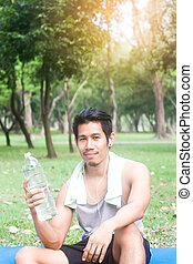 portrait of healthy young man holding bottle of water in nature