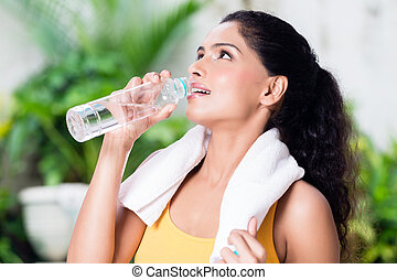 Portrait of healthy young woman drinking water during workout