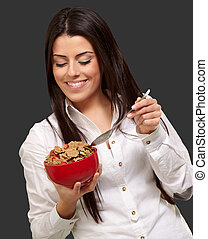 portrait of healthy young woman eating cereals over black