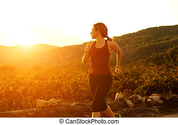 healthy young woman jogging outdoors in nature