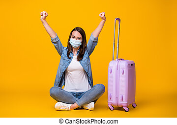 Portrait of her she nice attractive girl sitting crossed legs wearing safety mask rising hand up boarding pass pandemia infection prevention isolated bright vivid shine vibrant yellow color background