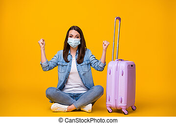 Portrait of her she nice attractive girl sitting crossed legs wearing safety mask waiting departure tourism boarding pass social distance isolated bright vivid shine vibrant yellow color background